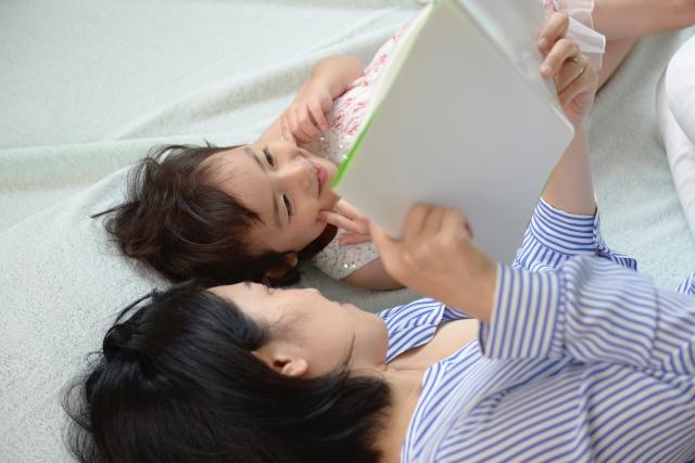 子供に本の読み聞かせをしている母親の写真