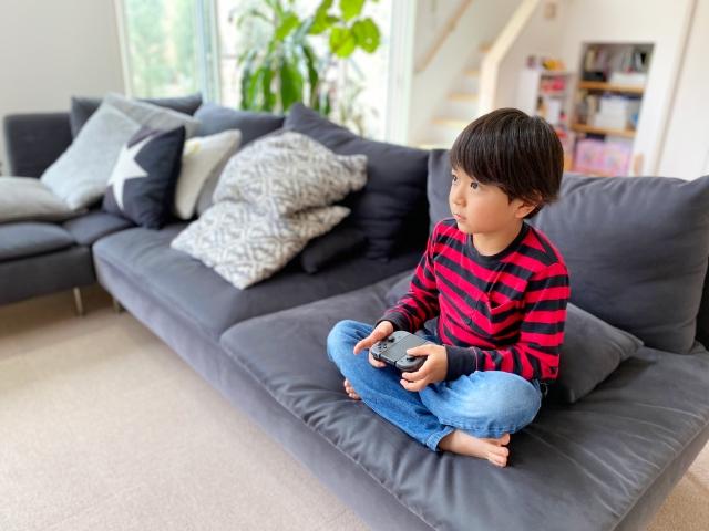 自宅のソファーに座ってテレビゲームをする男の子